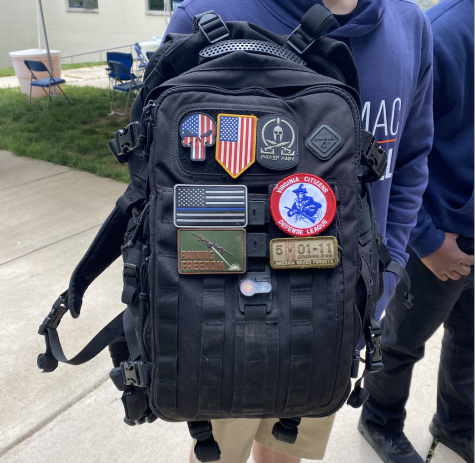 Potomac students backpack features many political patches after removal of Three Percenters emblem.